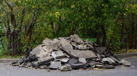 A pile of pieces of broken asphalt pavement on the edge of a green Park Banco de Imagens