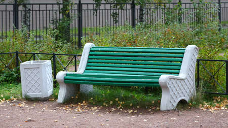 Green Park bench made of wood and concrete in the autumn Park