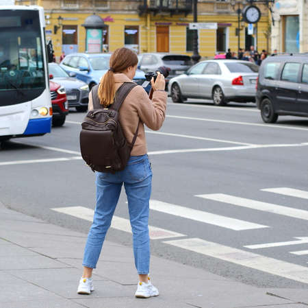 Girl photographer in jeans and white sneakers, Nevsky Prospekt, Saint Petersburg, Russia, October 2020