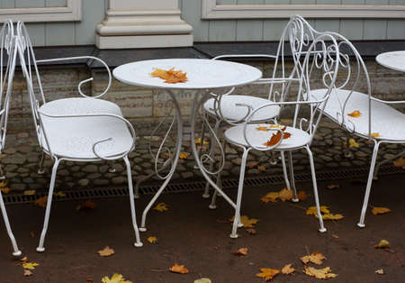 The white table and chairs of the summer cafe are covered with yellow autumn leaves