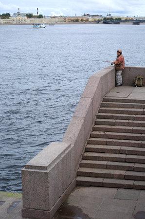 Fisherman with a fishing rod on the granite river embankment, Dvortsovaya Embankment, Saint Petersburg, Russia, October 2020