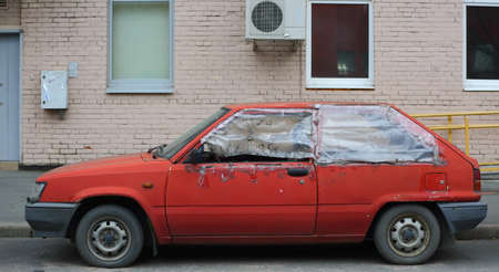 An old wrecked red hatchback car is parked outside the house Stock Photo