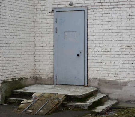 A gray metal front door set in a white brick wall