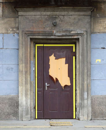 An old battered wooden front door in the wall of the house