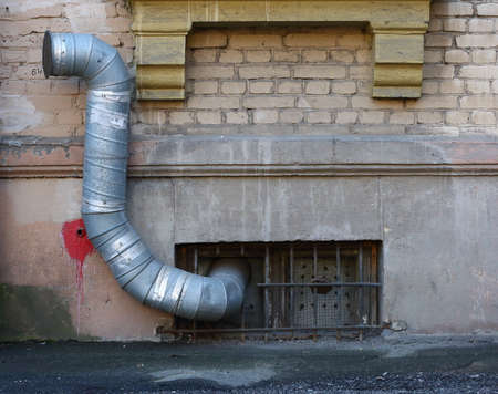 A basement window with a metal barrier and ventilation pipe Banco de Imagens