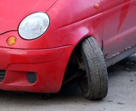Torn off wheel of a red passenger car due to a broken ball bearing Banco de Imagens