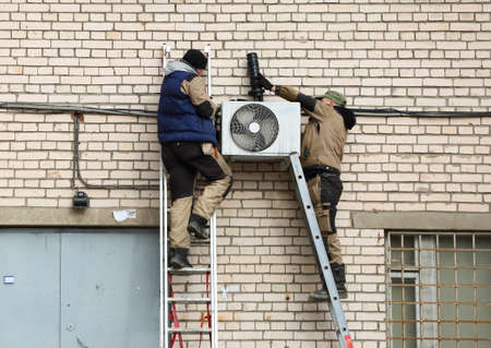 Two workers on a white brick wall install air conditioning