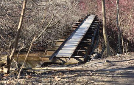 A narrow makeshift bridge across the river in the forest Banco de Imagens