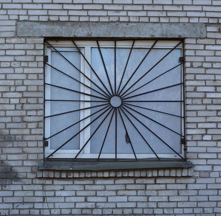 A window covered by a metal grate in a white brick wall