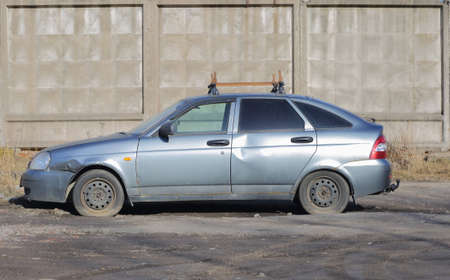 An old dented silver-colored car at a gray concrete fence