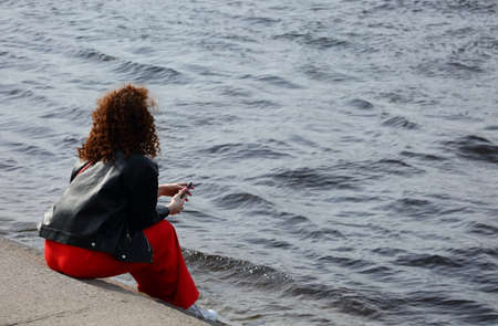 A girl in red pants sits on the steps of the river embankment, Admiralteiskaya Embankment, St. Petersburg, Russia, April 2021