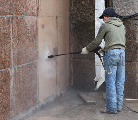 A cleaning worker washes the granite wall of a house with professional equipment, Nevsky Prospekt, Saint Petersburg, Russia, April 2021