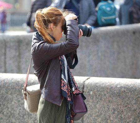 Blonde girl photographer on the street, Nevsky Prospekt, Saint Petersburg, Russia, April 2021