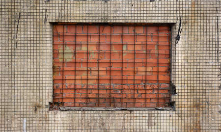 A red-bricked window in a white-tiled wall Banco de Imagens