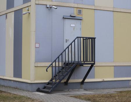 External metal staircase to a gray metal door in a multicolored wall, 24 Republican Ulitsa, Saint Petersburg, Russia, April 2021