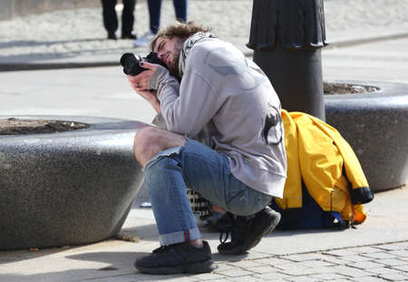 Street photographer in ripped jeans at work, Obvodny Canal Embankment, Saint Petersburg, Russia, April 2021