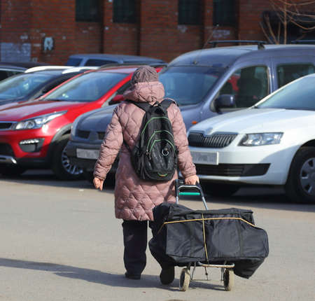 A woman in warm clothes with a backpack and a shopping cart walks through the parking lot, Iskrovsky Prospekt, Saint Petersburg, Russia, April 2021 Editorial