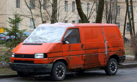 Old orange minivan without windscreen in the courtyard of a residential building
