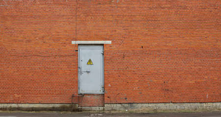 Metal door in red brick wall with electric power sign