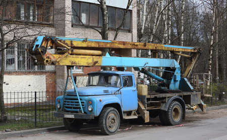 Special car with a folded lift in the courtyard of a residential building, ulitsa Kollontai, Saint Petersburg, Russia, April 2021