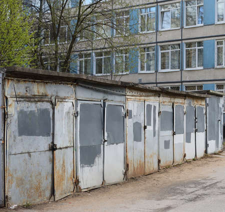 A row of garages with gray metal doors in the courtyard of an office building, ulitsa Kollontai, Saint Petersburg, Russia, April 2021 Editorial