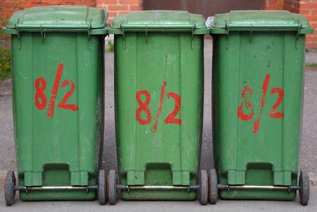 Three mobile green plastic dumpsters with red lettering