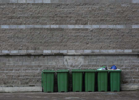 Six mobile plastic green dumpsters against the gray wall
