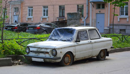 Old rusty white passenger car with flat wheels in the courtyard of a residential building, Malookhtinsky Prospekt, Saint Petersburg, Russia, May 2021 Editorial