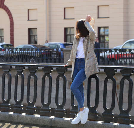 A girl in jeans, white sneakers and a checkered jacket at the cast-iron fence of the embankment, Griboyedov Canal embankment, Saint Petersburg, Russia, May 2021