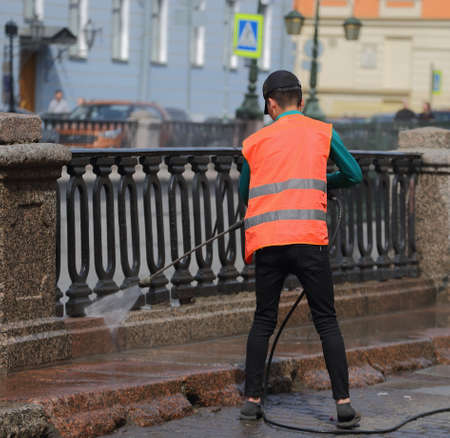 A cleaning worker in an orange vest uses a hose to wash the granite sidewalk of the embankment, Grboedova Canal embankment, Saint Petersburg, Russia, May 2021