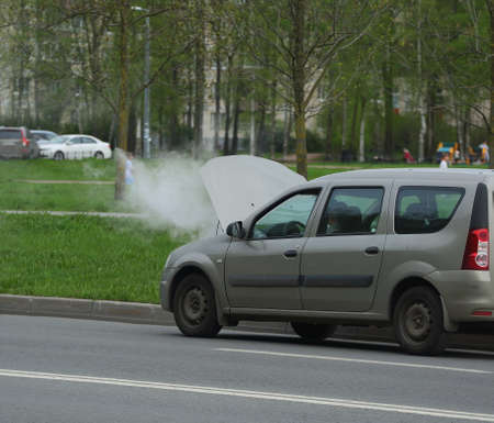 Water vapor from an open car hood on the road, Ulitsa Podvoyskogo, Saint Petersburg, Russia, May 2021 Editorial
