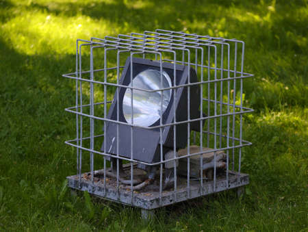 The ground searchlight in the green grass is covered with a metal mesh for safety