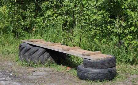 Improvised makeshift bench made of wooden planks and car tires Banco de Imagens