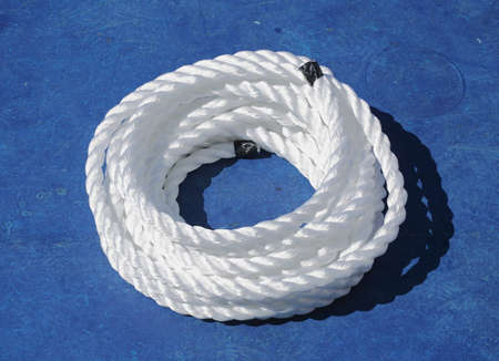 Coiled white ship rope on a blue background