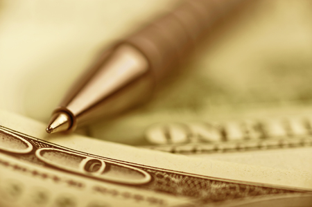 conclude: close-up pen on the money with shallow DOF