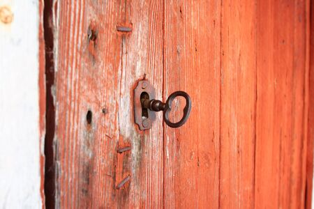 The old key is inserted into the keyhole of the old barn door photo