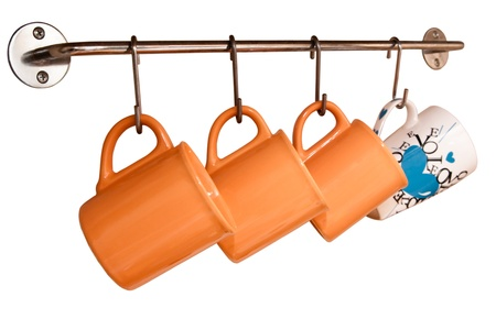Teacups orange hang on hooks on a white background