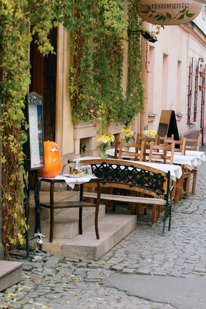 Tables restaurant on the street with green leaves on the walls and windows Stock Photo