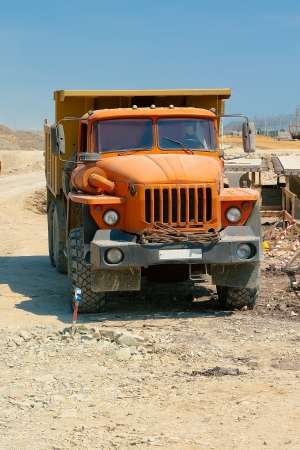 Powerful orange truck is on the construction area photo