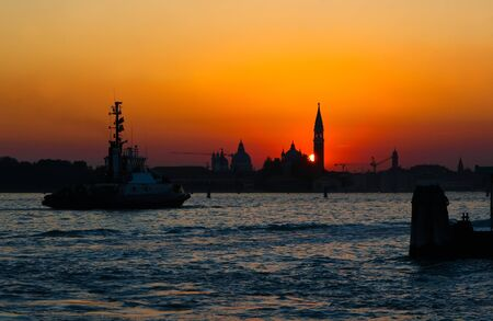 ship sails across the sea in the background of the sunset in Venice photo