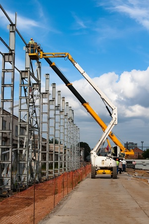 maneuverable: Hoist and crane involved in the installation of metal structures for construction of a building Stock Photo