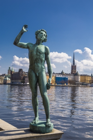 Statue of a man at the Town Hall in Stockholm against the Knights of the island and the lake Mälaren photo