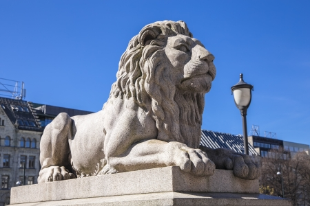 A statue of a reclining lion in the center of Oslo near the parliament