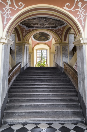 The main staircase of an old building with a beautiful painted ceiling