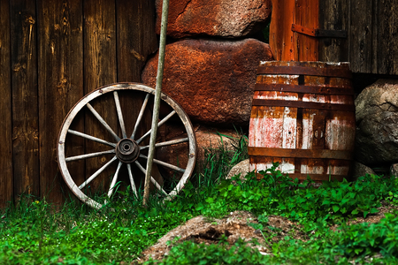 Still-life with an old wheel and barrel standing near the wall Stock Photo