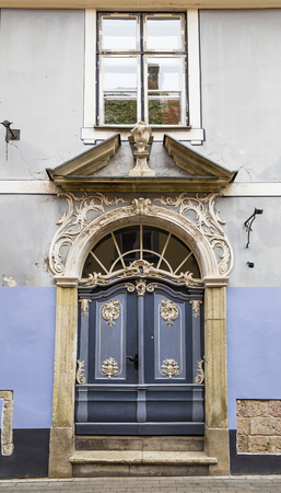 view of a wooden doorway: The front door to the old house with stucco decorations
