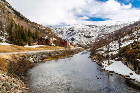 River with beautiful rocky shores and houses in the mountains  Norway photo