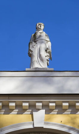 Sculpture of a woman on the roof of the building against the blue sky