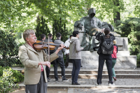 BUDAPEST, HUNGARY - APRIL 05 2014: Street violinist plays on the background of a sculpture of an unknown writer in the city park of Budapest