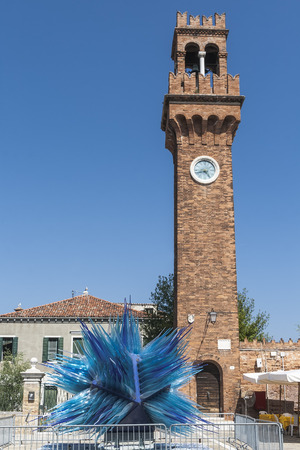 MURANO, ITALY - AUGUST 19, 2012: Modern installation of Murano glass in front of the old bell tower. Venice. Italy